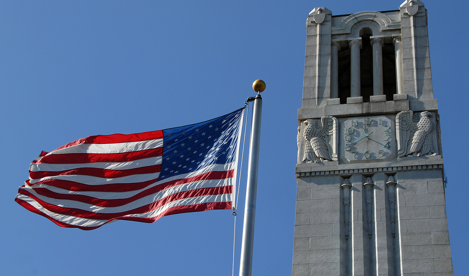 American flag waves in the Fall breeze next to the Belltower